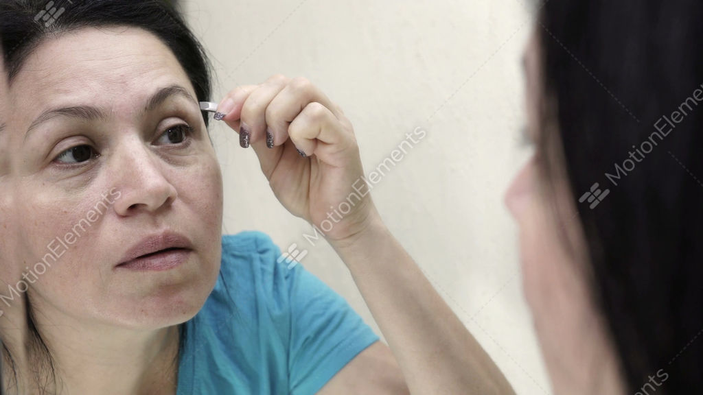 Woman Looking Into Mirror Plucking Eyebrows Handheld Stock Video