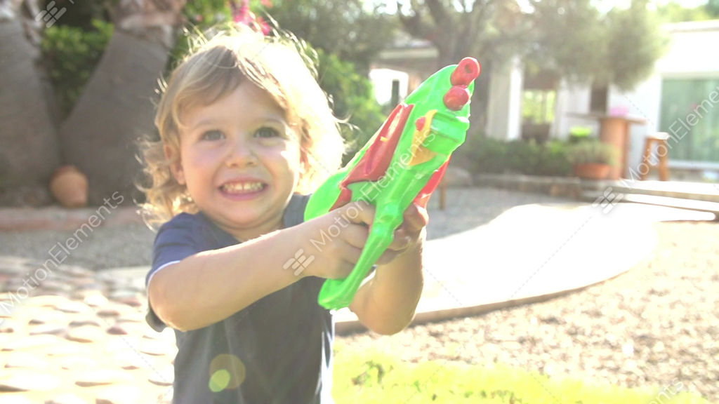 Slow Motion Shot Of Boy Squirting Water Pistol In Garden Stock Video Footage