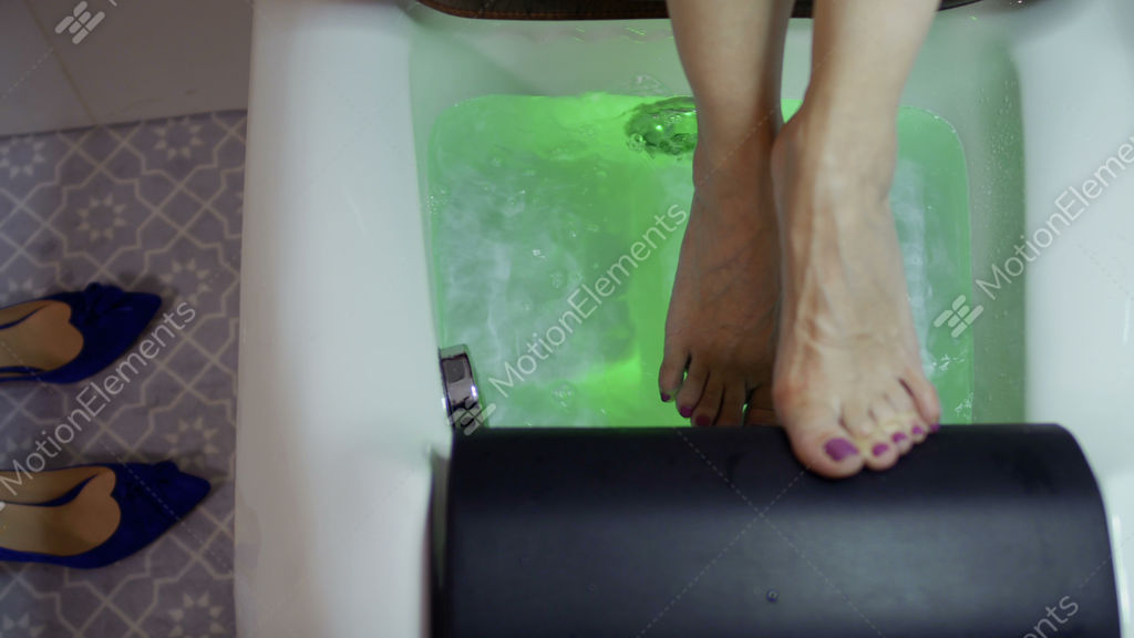 Female Relaxing Her Feet In A Small Bath With Bubbles And Colorful ...