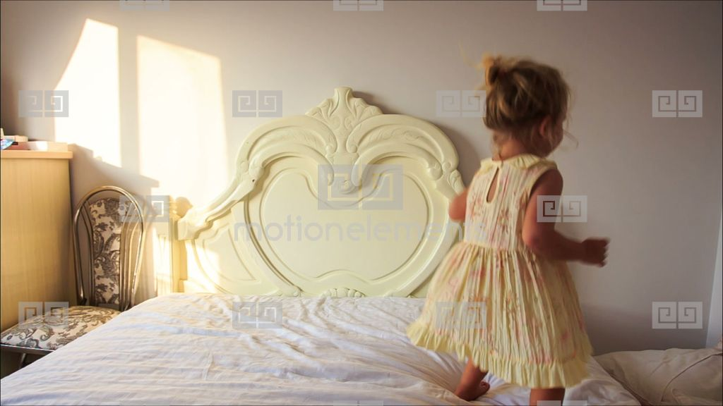 Little Girl Jumps Up And Down White Bed To Pillows On Floor Stock ...