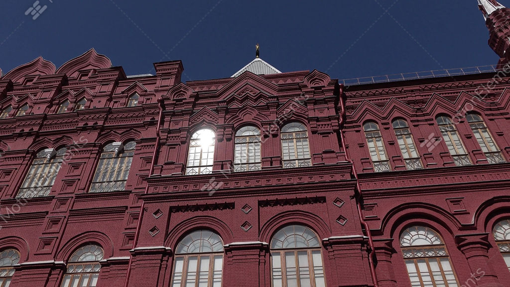 tracking shot of red brick facade with narrow arched windows