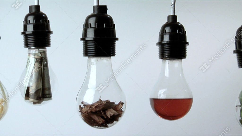 Light Bulbs Containing Plant Matter Folded Money And Red Liquid