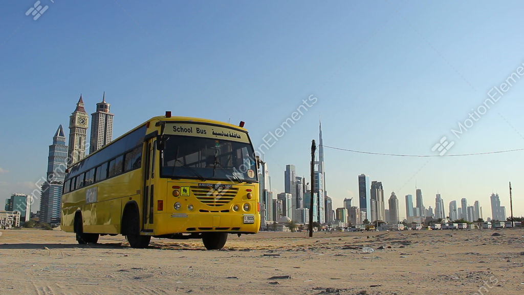 Single School Bus Stand At Vacant Sandy Plot Against Dubai Towers
