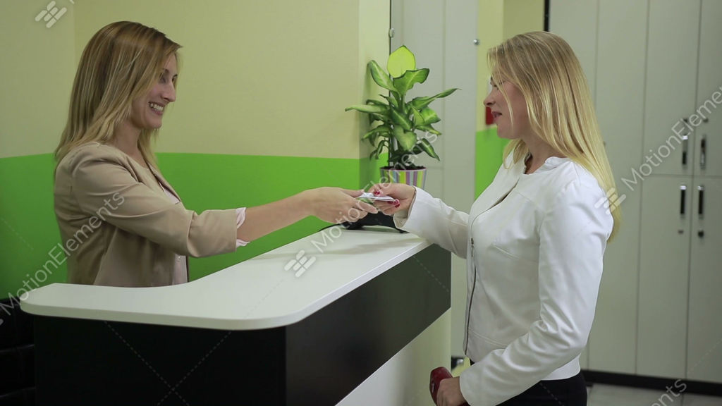 Happy woman paying with credit card at spa salon stock for X salon mulund rate card