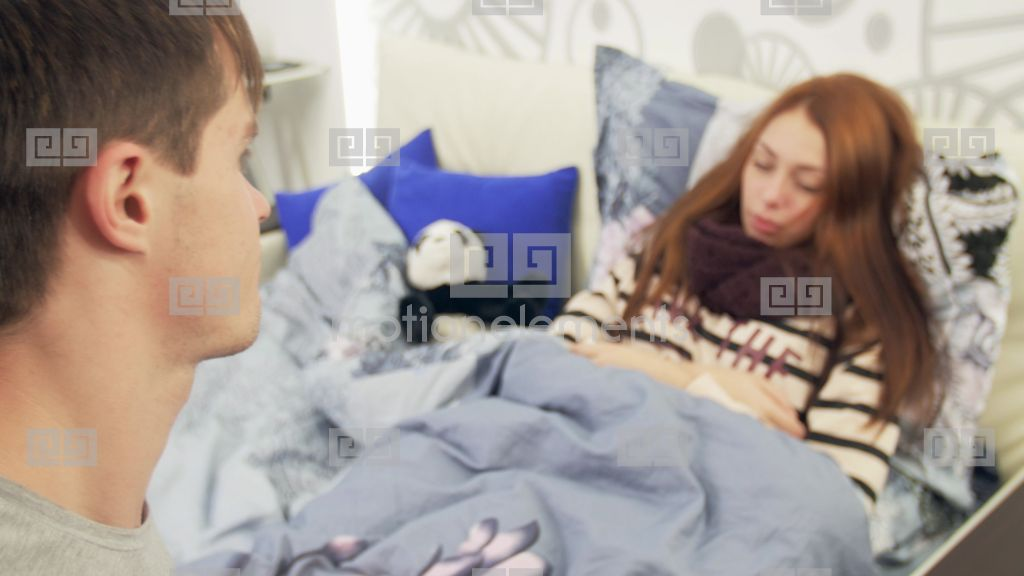 Husband Takes Care Of Sick Wife With Fever In Bed Stock